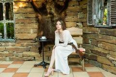 Menina bonita no vestido branco que levanta com um rifle de caça no fundo de uma pele do urso fotografia de stock