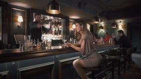 Menina bonita no vestido brilhante que faz o selfie que senta-se no contador da barra Na agitação farpada alta do barman do fundo video estoque