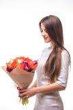 Menina bonita no vestido cinzento com as tulipas das flores nas mãos em um fundo branco Imagem de Stock