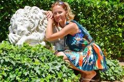 Menina bonita no vestido do verão perto da estátua do leão, conceito das férias de verão Imagens de Stock