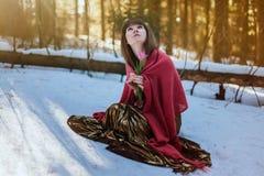 Menina bonita no vestido dourado que senta-se nas madeiras do sol da neve na primavera e na tulipa dos toques imagens de stock royalty free