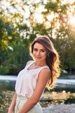 Menina bonita no vestido elegante e no sorriso encantador que levantam para o fotógrafo no parque de Yekaterinburg Imagem de Stock Royalty Free