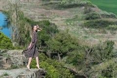 A menina bonita no vestido levanta na rocha na natureza foto de stock