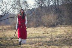 Menina bonita no vestido medieval vermelho que anda o prado foto de stock royalty free