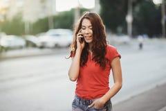 A menina bonita no vestido ocasional está falando em um telefone celular ao andar na rua da cidade em uma estadia do por do sol fotografia de stock royalty free