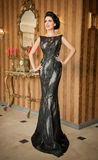 Menina bonita no vestido preto elegante que levanta na cena do vintage Mulher bonita nova que veste o vestido luxuoso Brunette se Imagens de Stock