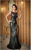 Menina bonita no vestido preto elegante que levanta na cena do vintage Mulher bonita nova que veste o vestido luxuoso Brunette se Fotografia de Stock Royalty Free