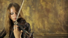 Menina bonita no vestido preto que joga o violino video estoque