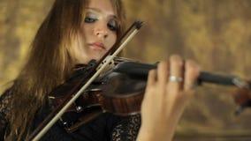 Menina bonita no vestido preto que joga o violino na filme