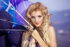 Menina bonita no vestido roxo com balões fotos de stock royalty free