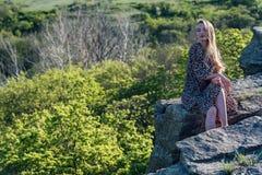 A menina bonita no vestido senta-se na rocha na natureza fotos de stock