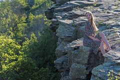 A menina bonita no vestido senta-se na rocha na natureza fotografia de stock