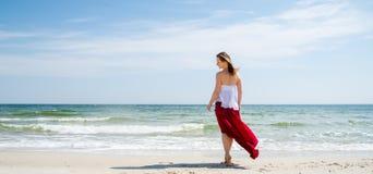 Menina bonita no vestido vermelho pelo mar Imagens de Stock
