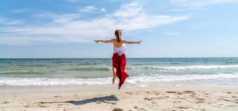Menina bonita no vestido vermelho pelo mar Foto de Stock
