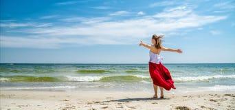 Menina bonita no vestido vermelho pelo mar Fotografia de Stock Royalty Free