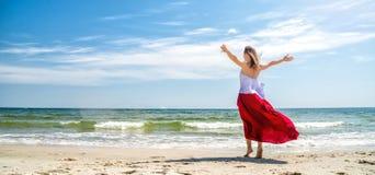 Menina bonita no vestido vermelho pelo mar Fotos de Stock