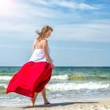 Menina bonita no vestido vermelho pelo mar Fotos de Stock Royalty Free