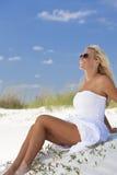 Menina bonita nos óculos de sol brancos do vestido na praia Fotos de Stock