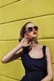 Menina bonita nos óculos de sol perto da parede amarela Fotos de Stock Royalty Free
