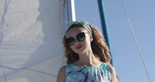 Menina bonita nos óculos de sol que levantam em um iate no verão O vento funde o cabelo encaracolado vídeos de arquivo