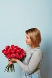 Menina bonita nos macacões com as rosas vermelhas nas mãos em um fundo azul As mãos do ` s das mulheres estão guardando um ramalh Fotos de Stock