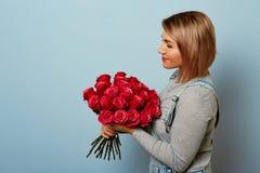 Menina bonita nos macacões com as rosas vermelhas nas mãos em um fundo azul As mãos do ` s das mulheres estão guardando um ramalh Imagens de Stock Royalty Free