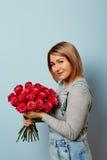 Menina bonita nos macacões com as rosas vermelhas nas mãos em um fundo azul As mãos do ` s das mulheres estão guardando um ramalh Imagem de Stock
