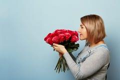 Menina bonita nos macacões com as rosas vermelhas nas mãos em um fundo azul As mãos do ` s das mulheres estão guardando um ramalh Foto de Stock Royalty Free