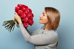 Menina bonita nos macacões com as rosas vermelhas nas mãos em um fundo azul As mãos do ` s das mulheres estão guardando um ramalh Fotos de Stock Royalty Free