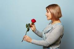 Menina bonita nos macacões com as rosas vermelhas nas mãos em um fundo azul As mãos do ` s das mulheres estão guardando um ramalh Fotografia de Stock Royalty Free