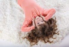 Menina bonita nos pijamas nas horas de dormir imagens de stock