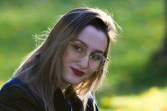 Menina bonita nos vidros com o batom vermelho que olha na câmera Iluminação natural do contorno foto de stock royalty free