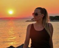 Menina bonita nos vidros no por do sol em Europa foto de stock royalty free