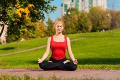 A menina bonita nova é contratada na ioga, fora em um parque Imagens de Stock Royalty Free