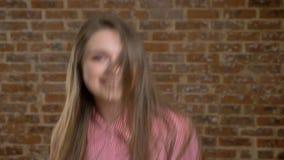 A menina bonita nova é lançando ele cabelo traseiro, saltando, dançar, olhando na câmera, fundo do tijolo filme