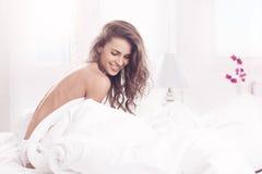 A rapariga acordou e sentando-se em uma cama Imagem de Stock