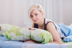 A menina bonita nova acordou no close-up da cama imagem de stock royalty free