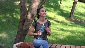 A menina bonita nova agita uma garrafa plástica com água, sentando-se em um banco na máscara de uma árvore filme