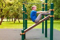 A menina bonita nova balança a imprensa no gym fotos de stock