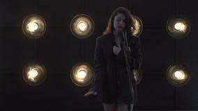 A menina bonita nova canta Cantor novo que canta em um microfone Retrato próximo acima do cantor filme