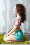 Menina bonita nova com assento do cabelo encaracolado Fotografia de Stock