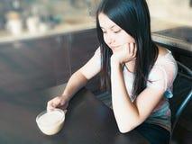 A menina bonita nova com cabelo longo escuro senta-se em uma tabela com uma xícara de café e sonhos sobre algo imagens de stock