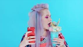 A menina bonita nova com cabelo roxo faz o selfie em um smartphone vermelho vídeos de arquivo