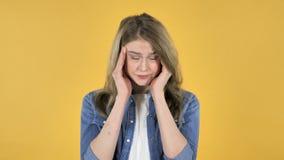 Menina bonita nova com dor de cabeça no fundo amarelo video estoque