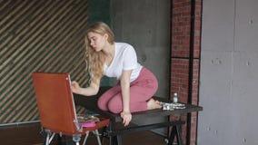 Menina bonita nova com escova e paleta que senta-se perto da imagem do desenho da arma??o Arte, faculdade criadora, passatempo, p filme