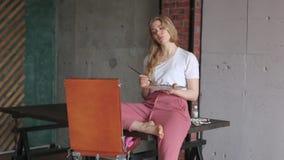 Menina bonita nova com escova e paleta que senta-se perto da imagem do desenho da arma??o Arte, faculdade criadora, passatempo, p vídeos de arquivo
