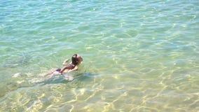 Menina bonita nova com o cabelo longo que flutua no mar transparente puro video estoque