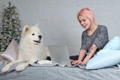 Menina bonita nova com o cabelo louro que trabalha com o portátil no sof foto de stock