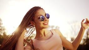 A menina bonita nova com teme dançar em um parque Mulher bonita nas calças de brim e nos óculos de sol que escuta a música e video estoque