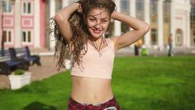 A menina bonita nova com teme dançar em um parque Mulher bonita nas calças de brim que escuta a música e que dança durante a video estoque